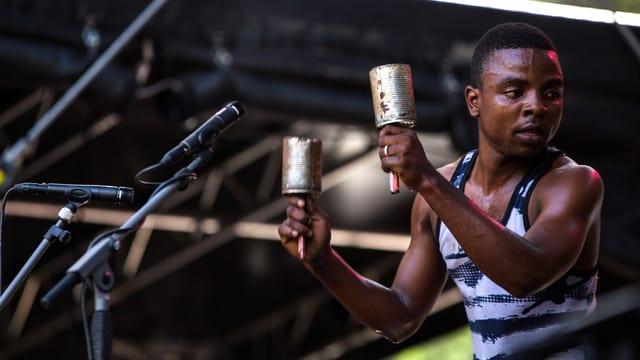 Ein dunkelhäutiger Mann steht auf einer Bühne und spielt vor zwei Mikrofonen zwei Rasseln, die aus Blechbüchsen gebaut wurden.
