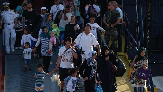 Menschen am Hafen mit Gepäck.