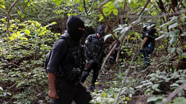 Vermummte Polizisten im Wald