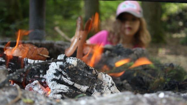 Glühende Kohlen im Vordergrund, hinter dem Feuer ein junges Mädchen