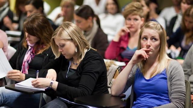 Arbeitende und nachdenkende Studierende in einem Hörsaal der Uni Basel.