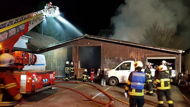 Feuerwehrleute bekämpfen Brand, im Vordergrund eine Drehleiter