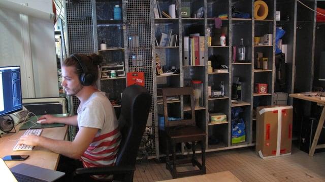 Ein Mann arbeitet am Computer im Hintergrund ein Büchergestell