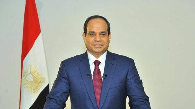 Der Präsident steht vor der ägyptischen Fahne.