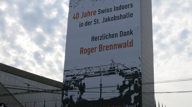 Blick auf die Aussenfassade der St. Jakobhalle mit einer herzlichen Widmung an Roger Brennwald.