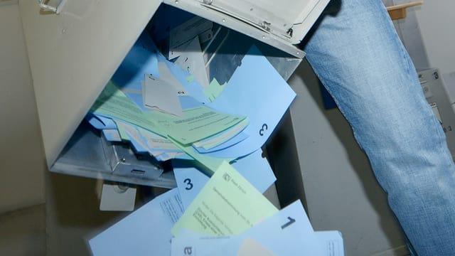 Wahlzettel werden aus einer Urne geleert.