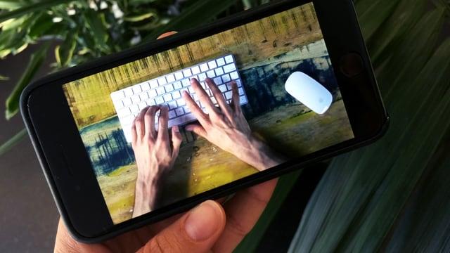 Hand hält Smartphone in der Hand, darauf Hände auf einer Tastatur