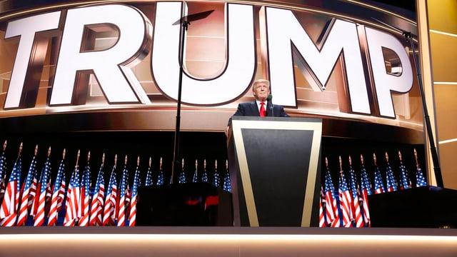 Donald Trump am Rednerpult – dahinter steht in grossen Lettern Trump.