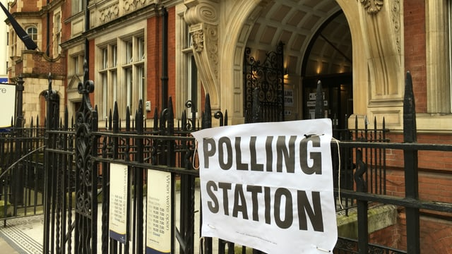 "Il maletg mussa in grond placat cun si ""Polling Station"" avant il biro da votar"