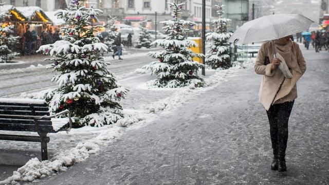 Passantin geht durch das verschneite Zürich.