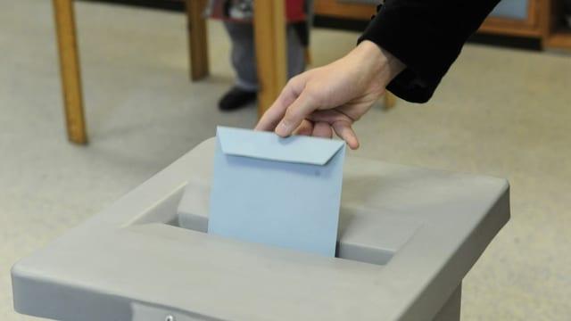 Jemand steckt ein Couvert in eine Wahlurne in Österreich