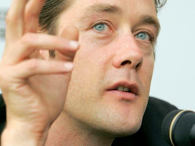 Ein Regisseur spricht in ein Mikrofon, die Hand in der Luft.