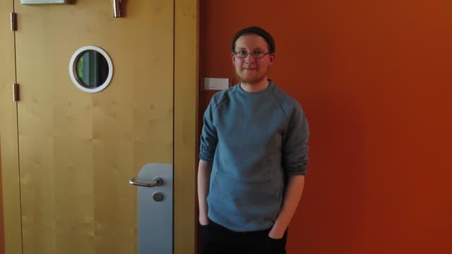 Junger Mann mit grauem Pullover, schwarzer Mütze und Brille