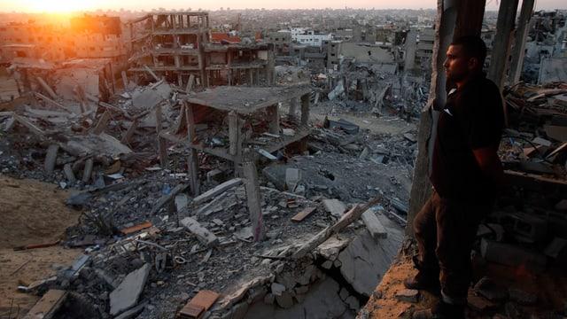 Mann schaut aus einem Haus auf die zerstörte Stadt.