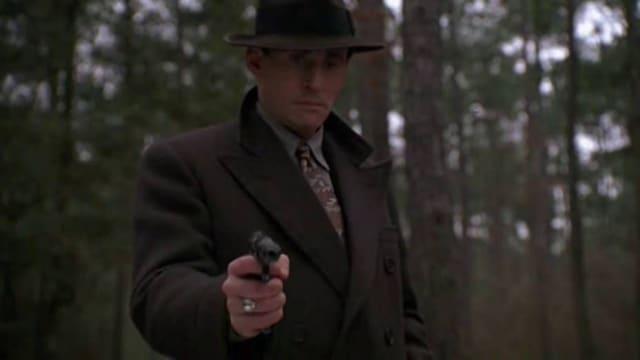 Ein Mann mit Hut zielt mit einer Pistole in Richtung Kamera