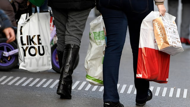 Menschen tragen Einkaufstaschen.
