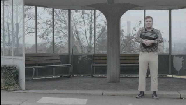 Ein Posträuber steht mit einem Abfallsack, gefüllt mit Tausendernoten an der Busstation. (Filmausschnitt)