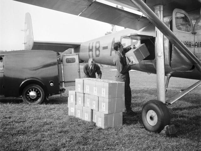 Männer laden Kisten in Flugzeug