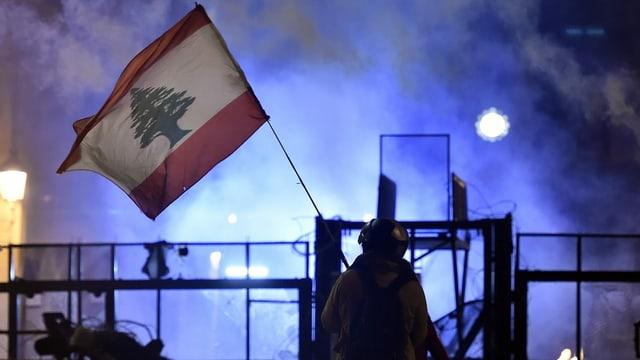 Ein Demonstrant hält eine Libanon-Flagge hoch.