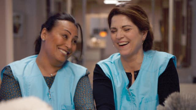 Zwei Frauen in blauen Kitteln lachen gemeinsam.