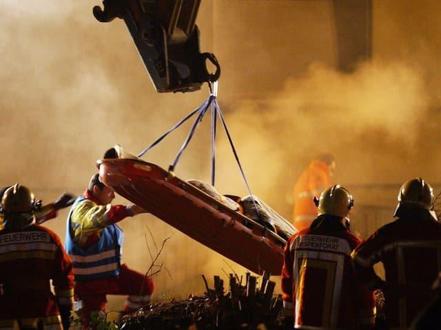 Feuer und Rauch. Kran hebt eine Bahre, darum stehen Feuerwehrmänner.