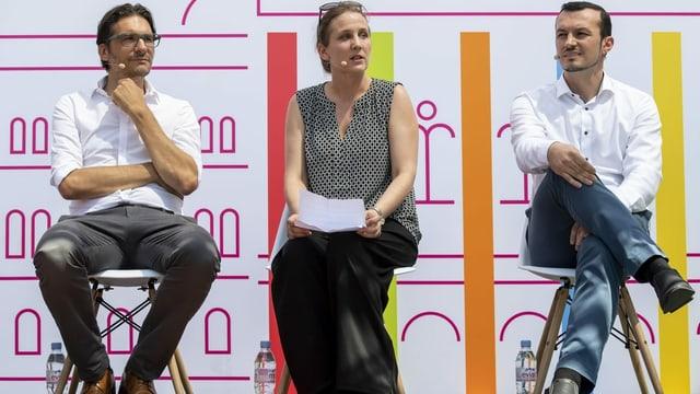 Zwei Männer und eine Frau sitzen vor einem Plakat auf Stühlen.