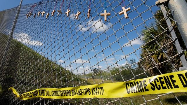 Zaun vor der Schule in Florida. Daran sind ein Absperrband und Holzkreuze befestigt.