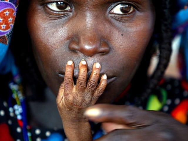 Unternährtes Kind hält seine Hand an den Mutter der Mutter, Niger 2005.