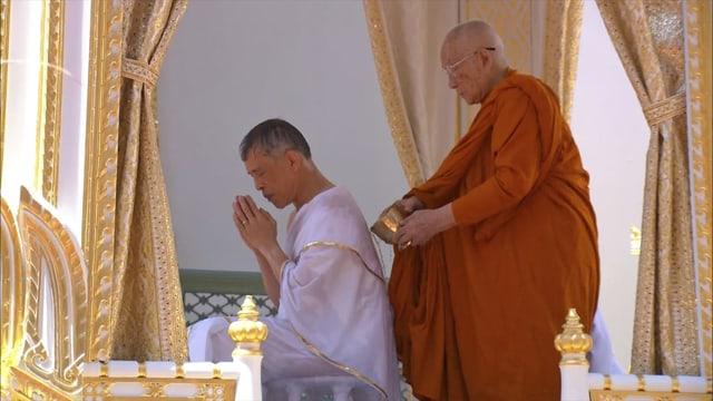 Mönch in oranger Robe steht hinter dem König und salbt ihn.