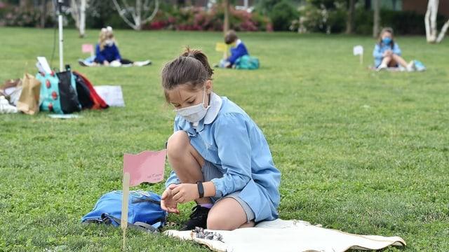 Schulkinder mit Abstand auf einer Wiese