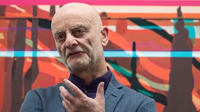 Uli Sigg gestikuliert vor einem Gemälde aus seiner Sammlung.