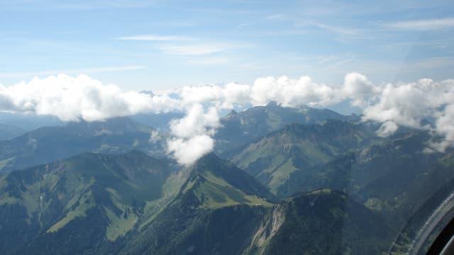 Flugaufnahme auf Berglandschaft: An den Gipfeln hat es kleine Wolken, der Himmel ist sonst blau.