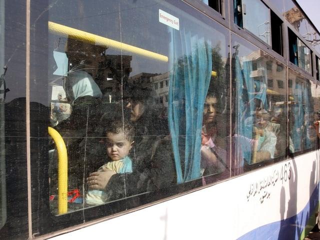 Kind schaut aus einem Busfenster