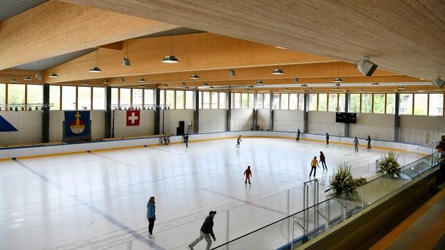 Eishalle mit Holzbalken und einigen Schlittschuhläufern.