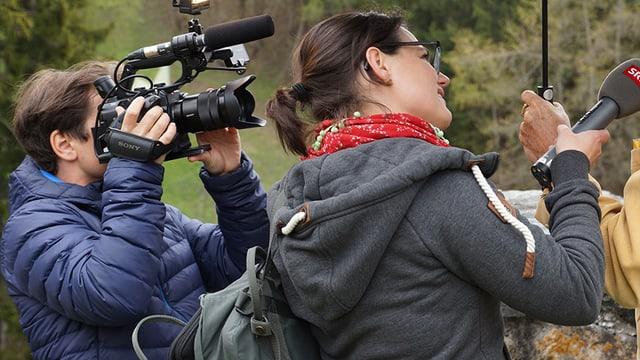 Ein Kamermann und eine Radioreporterin bei der Arbeit.