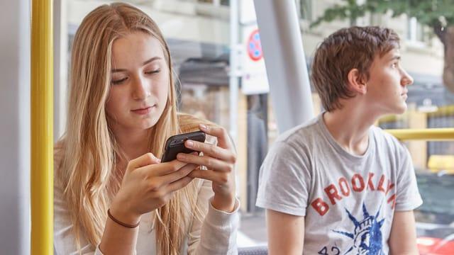 Ein Mädchen tippf auf ihrem Smartphone. Neben ihr sitzt ein Junge.