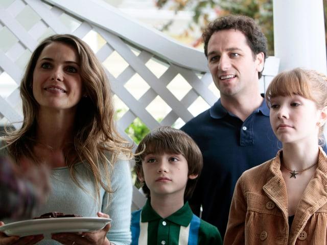Elizabeth und Philipp Jennings bringen mit ihren Kindern den Nachbarn Kuchen.
