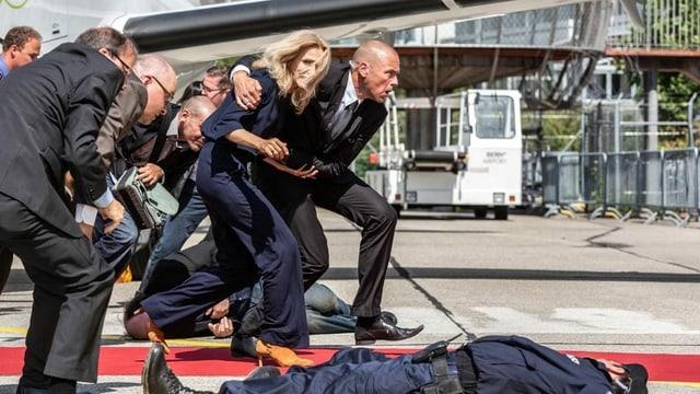 Eine Blonde Dame flüchtet in Begleitung von Sicherheitspersonal von einem Anschlag