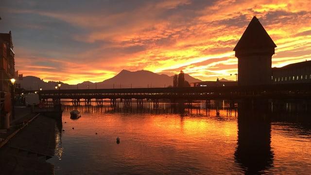 Kapellbrücke in Luzern mit Pilatus und einem goldenen Morgenhimmel.