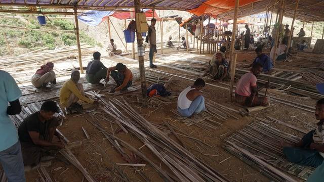 Menschen in einer provisorischen Unterkunft, bauen selber ihre Hütten.