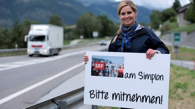 """Sabine Dahinden mit dem Schild """"Schweiz Aktuell am Simplon"""" an einer Strasse"""