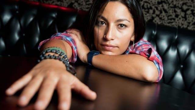 Ana Tijoux hat ihre Hand auf dem Tisch.
