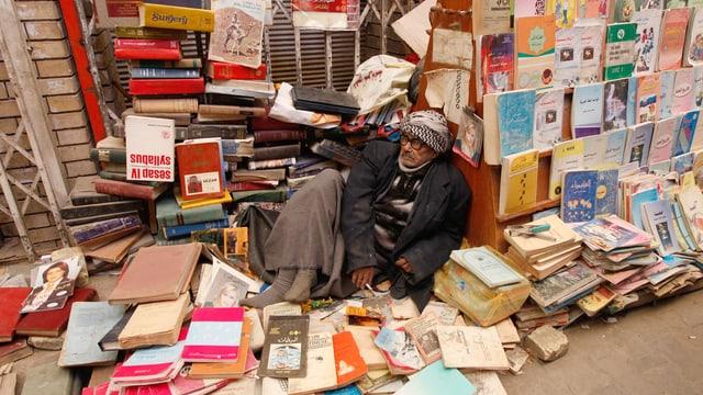 Ein Mann inmitten seiner Bücher auf der Strasse.