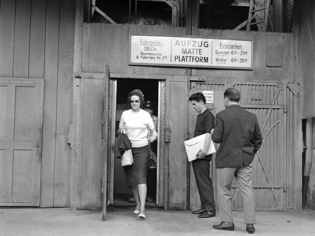Frau steigt aus dem Lift aus, zwei Männer warten.