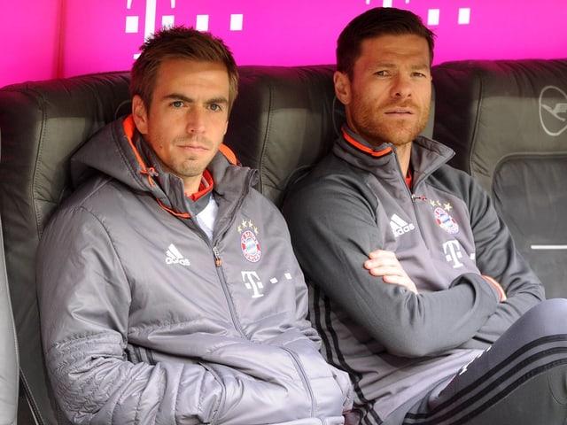 Philipp Lahm (links) und Xabi Alonso sitzen auf der Spielerbank.