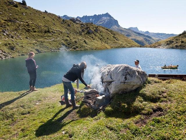 Eine Gruppe grilliert im Sommer an einem Bergsee.