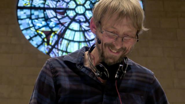 Mann mit Kopfhörern vor Kirchenfenster