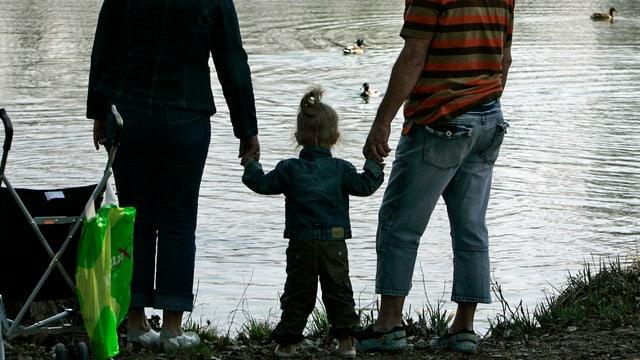 Eine Mutter und ein Vater halten ihr Kleinkind an der Hand und beobachten Enten im See.
