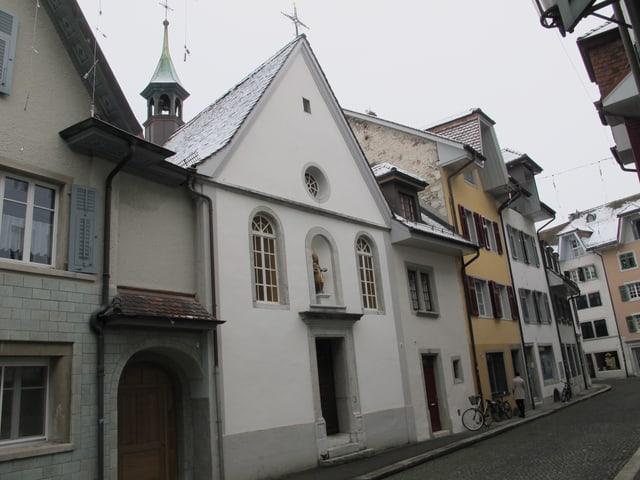 Kapelle in einer Altstadt, rundherum Häuser