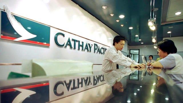 Ein Mitarbeiter von Cathay Pacific ist einem Kunden behilflich.